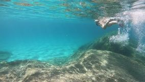 Slow motion of a beautiful young woman in a black bikini taken from underwater swimming in the blue water with mask and snorkeling. On the seabed of rocks and stock footage