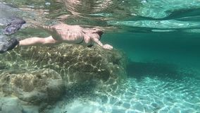 Slow motion of a beautiful young woman in a black bikini taken from underwater swimming in freestyle and dolphin in the transparen. T water with mask and stock video footage