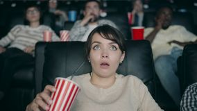 Slow motion of beautiful woman watching film in cinema with open mouth drinking