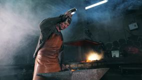 Slow motion of a blacksmith forging incandescent metal. HD stock footage
