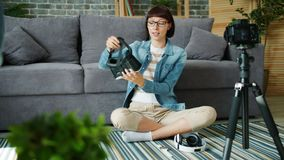 Slow motion of blogger recording video about virtual reality glasses at home. Slow motion of blogger young woman recording video about virtual reality glasses stock footage