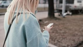 Slow motion blonde woman reading from smartphone. Girl browsing websites while walking in the city. Point of view shot. Slow motion blonde woman in blue coat stock video