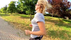 Woman outdoor run. Slow motion blonde woman in tight leggings doing jogging on a city park road. Healthy life concept. Cardio jogging workout girl training stock video
