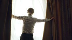 Slow motion of blonde woman unveil curtains in hotel room at the morning and looking into window