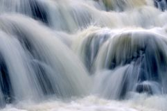 Slow motion blue waterfall. Background of cascading waterfall with slow motion blur effect royalty free stock photos