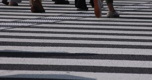 A slow motion of body parts of walking people on the crossing at the business town