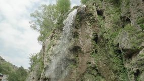 Slow motion bottom view of water stream falling from cliff stock video footage