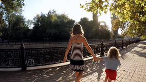 SLOW MOTION. Boy and girl holding hands. SLOW MOTION. Little boy and girl 11 years walking in a city park along the river. Children hold hands and through stock footage