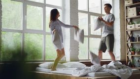 Slow motion of boyfriend and girlfriend jumping on double bed, fighting pillows and laughing together having fun in stock video