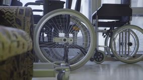 Slow motion of bunch of wheelchairs with white wheels put next to windows. stock footage