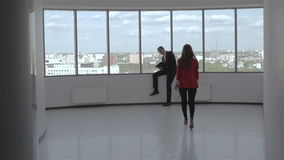 Slow motion. Businessman and businesswoman discussing a business decision in the hall near the window. Young woman in red jacket walking the hall to a man in a stock video