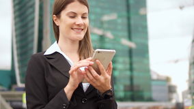 Slow Motion Businesswoman using smart phone in city downtown, professional female browsing reading. Slow Motion Young successful businesswoman in suit using stock footage