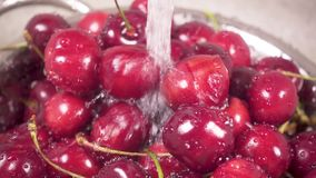 Slow motion cherry in colander under water. Slow motion the camera moves on a beautiful sweet cherry in a metal colander in a sink under a stream of water stock video footage