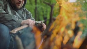 Slow Motion Of Casual Strong Man Works with Ax and Wood near Warm Bonfire in Camp in Wild Deciduous Forest. stock video