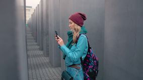 Slow Motion Caucasian girl tourist with a backpack in the center of Berlin in the autumn. Makes a photo of Memorial to. The Murdered Jews of Europe on a stock video footage
