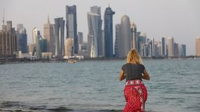 Woman by Doha Skyline. SLOW MOTION: Caucasian woman jumping on the Doha West Bay in Qatar. Blonde tourist enjoys Doha Downtown from West Mound-Skyline viewpoint stock footage
