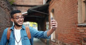 Slow motion of cheerful Arabian man taking selfie with smartphone outdoors. Slow motion of cheerful Arabian man taking selfie with smartphone camera outdoors stock footage