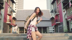 Slow motion - Cheerful beautiful young Asian backpacker blogger woman feeling happy dancing on street while traveling. stock video footage