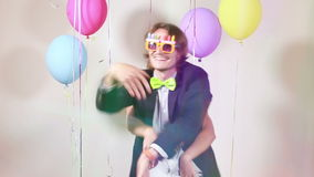 Slow motion of cheerful couple dancing funny in photo booth. Young cheerful couple dancing funny in photo booth, graded, in slow motion stock video footage