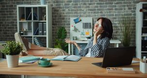 Slow motion of cheerful girl talking on mobile phone at work smiling. Enjoying conversation sitting at desk with legs on table. People, job and youth concept stock footage