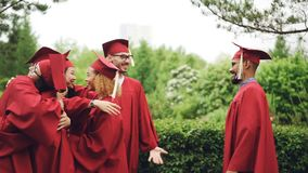 Slow motion of cheerful girls and guys graduating students hugging and shaking hands wearing hats and gowns enjoying stock footage