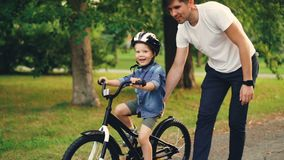 Slow motion of cheerful guy caring father teaching his small son to ride bicycle in park. Cute boy is cycling while. Slow motion of cheerful guy caring father stock footage