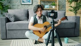 Slow motion of teenage blogger talking for camera holding guitar at home. Slow motion of cheerful teenage blogger boy talking for camera holding guitar sitting stock video