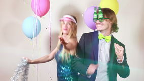 Slow motion of cheerful woman and man dancing in photo booth. Cheerful beautiful woman and smiling man dancing in party photo booth, graded, slow motion stock video footage