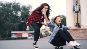 Slow motion of cheerful young women friends riding skateboard sitting on it and pushing it in the city on summer day. Friendship, modern lifestyle and stock footage