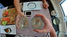 Slow motion cheers. Slow Motion: Aerial view of two white wine glasses while doing cheers to celebrate an event in a japanese sushi restaurant interior, set stock footage