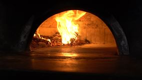 Slow motion chef using metal shovel for lights a fire into wood stone oven stock video footage