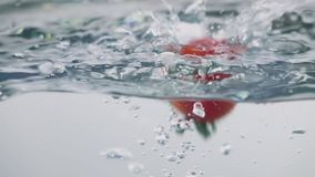 Slow-motion cherry tomatoes through water. Slo-motion cherry tomatoes through water stock video