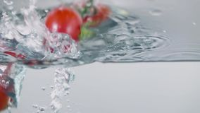 Slow-motion cherry tomatoes through water. Slo-motion cherry tomatoes through water stock video footage
