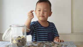 Children education concept with money jar. Slow motion child drops coin money into glass jar, financial concept stock video footage