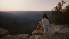 Slow motion cinematic shot, happy young woman with hair blowing in the wind sitting at breathtaking sunset Grand Canyon. stock footage