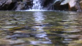 Slow Motion clear pond with waterfall in the background. stock video