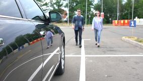 Slow motion of a couple walking through a car park stock video footage