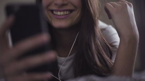 Slow motion close-up footage of young female lies in a bed and uses smartphone, girl listens to the music through stock footage