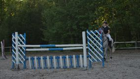 SLOW MOTION, CLOSE UP, LOW ANGLE: Horsegirl riding strong brown horse jumping the fence in sunny outdoors sandy parkour. Dressage arena. Competitive rider stock footage
