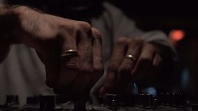 Dj hands mixing at night. Slow motion close up of male dj hands with golden rings mixing a track on an audio console in a club at night