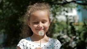 Slow Motion Close-Up Shot of Cute Little Girl Carefree Blowing a Dandelion Outdoors on a Sunset. Concept of Happy. Slow Motion Close-Up Shot of Cute Little Girl stock video footage
