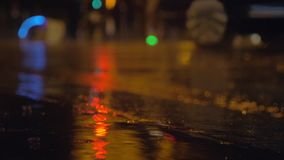 Drizzle and puddles on the asphalt with lights reflection. Slow motion close-up shot of raindrops falling into puddle in the street in the evening. City and car stock footage
