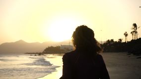 Slow Motion Close up silhouette of Young Woman jogging on a beach with hair blowing in wind looking at sunset over ocean stock video