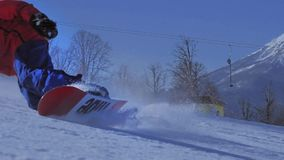SLOW MOTION CLOSE UP: Snowboarder carving on perfectly groomed snow in mountain ski resort stock video