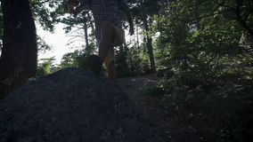 SLOW MOTION, CLOSE UP: Unrecognizable courageous male hiker climbing mountaintop, walking off trail on dangerous rocky