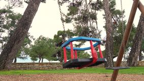 Swing at the playground. Slow motion close up video of empty swing at the playground swinging stock video footage
