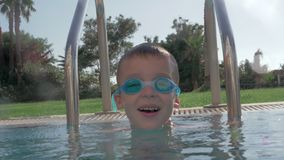 Cheerful child in goggles bathing in outdoor swimming pool stock video