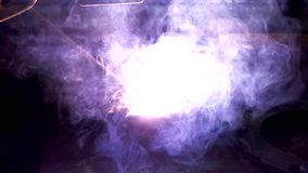 Slow motion close up worker welding steel with smoke and colourful of lights stock video footage