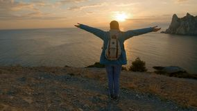 SLOW MOTION, CLOSE UP: Young female standing on the edge of the cliff and raising her hands up against high rocky stock footage