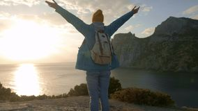 SLOW MOTION, CLOSE UP: Young female standing on the edge of the cliff and raising her hands up against high rocky stock video